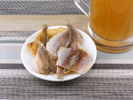 smoked fish and cup of beer on a background photo