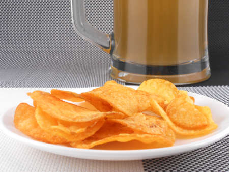 Mug of Fresh Beer and plate with Pile potato chips photo