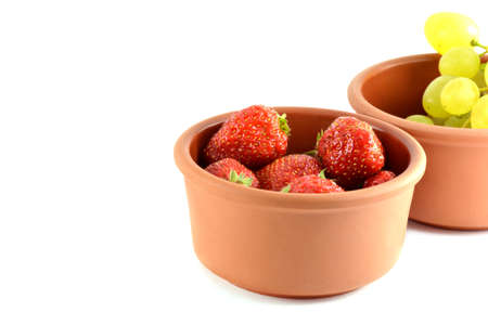 Grapes and strawberries in a bowl, isolated on white photo