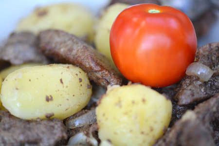Fried pork liver with tomatoes and potatoes photo