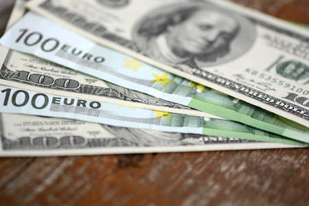 packs of dollars and euro money on wooden background photo