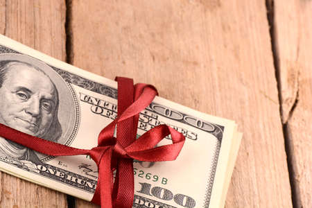 christmas debt: dollars wraped up with a red ribbon isolated on white background