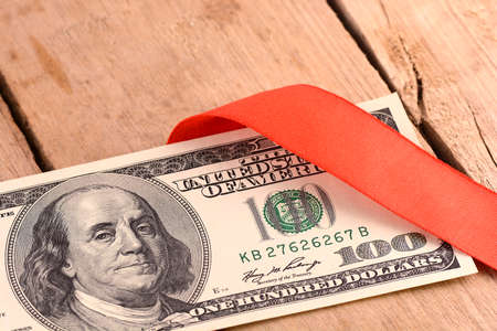 red bills: One Hundred Dollar Bills Wrapper in Red Ribbon Stock Photo