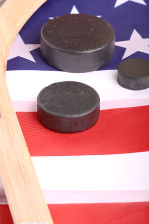 infer: Hockey equipment including a stick and puck on an American flag to infer a patriotic American sport. Stock Photo