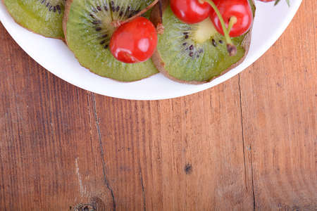 fruit plate: health fruit with cherry, kiwi slices on wooden plate