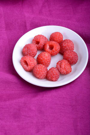 Ripe sweet raspberries in white bowl on pink material. Close up
