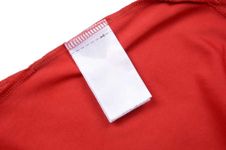 White blank clothing tag label on shirt fabric texture background