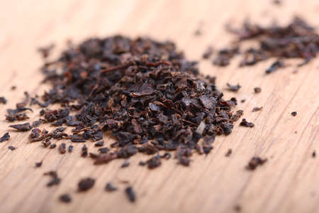 Earl grey black dry tea leaves on wooden plate close up