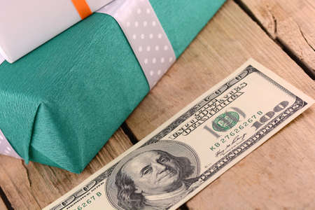 Dollars money along with a gift, a symbol of the crisis, venality, hoarding and wealth. American money on wooden background.