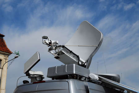 parabola: Shot of the part of TV van, cropped to the roof, showing high-tech equipment for TV transmission. Antenna,transmitter and signal receiver Stock Photo