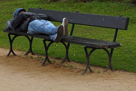 Hombre joven sin hogar durmiendo en el parque  Foto de archivo