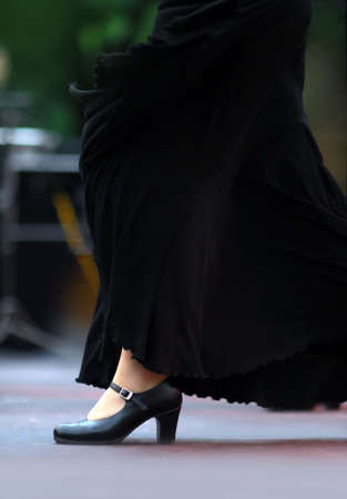 Flamenco dancer in the movement. Black skirt and black shoes. Focus on shoe. Background out of focus.