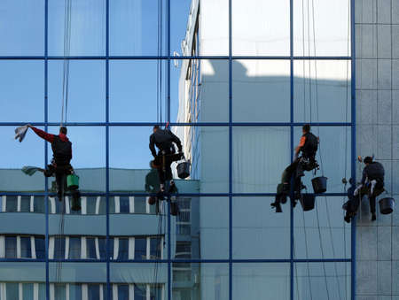 4 workers cleaning glass facade of modern building.