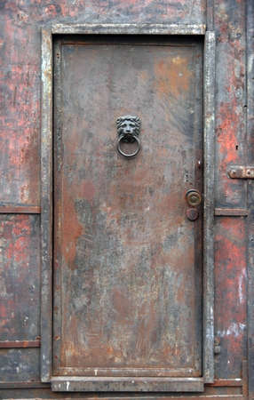 Old, rusty, heavy, industrial iron door.