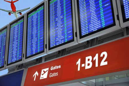timetable: Orario schermi in aeroporto. Flying getto in un angolo. Editoriali