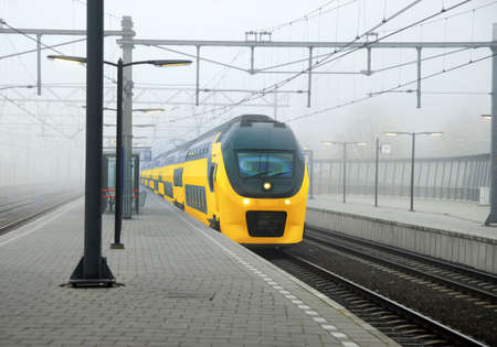 Yellow Dutch train and central station platform in Amsterdam