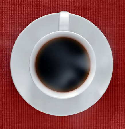 Cup of hot espresso viewed from top. Some steam visible