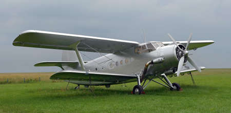 aerodrome: An old silver antonov standing on the grass aerodrome