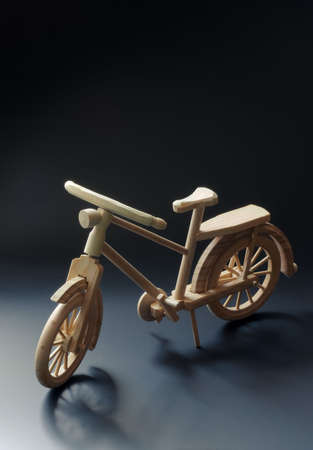 Bicycle small wooden toy model. Dark background with wheel shadows. Stock Photo - 7401967