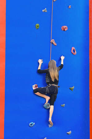 Young girl climbing up secured with rope. Wall is a blue balloon with mounted steps photo