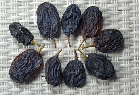 Group of dry seedles grapes on light gray mat. Stock Photo