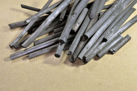 Natural charcoal sticks used for artistic drawing on paper. Art paper as background.