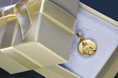 Religious gold pendant with Jesus showing heart. Typical gift for first communion for Catholics.