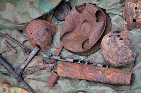 Still life of old military weapons digged out from the ground. Second world war. British automatic gun Sten on the bottom left side.