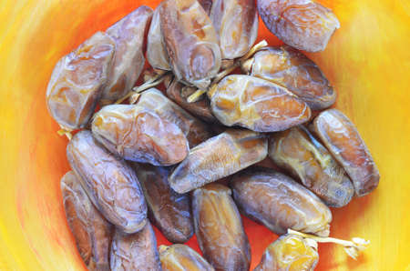 Dry dates on orange plate macro image.