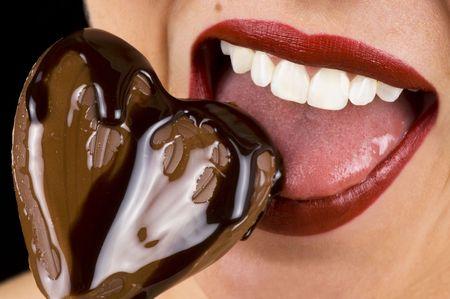 femme bouche ouverte: Une belle jeune femme piqueurs dans un c?ur chocolat