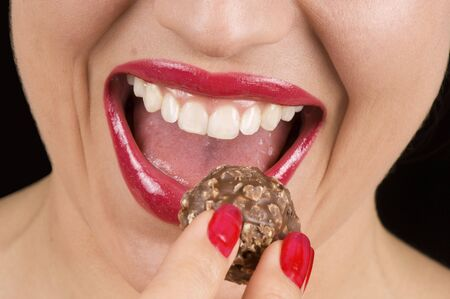 Macro of a beautiful woman biting chocolate candy photo