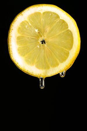 Drops of juice falling of the lemon photo