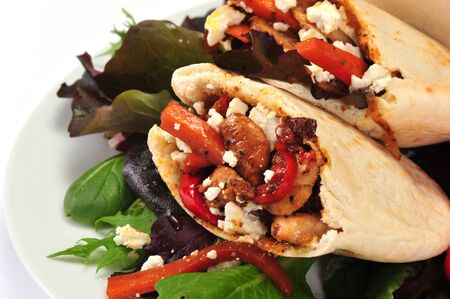 Pitta bread on salad leaves filled with a chi?ken, vegetables and feta cheese photo