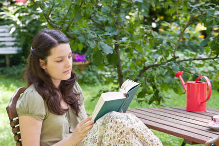 Young woman is reading in a garden Stock Photo - 15077883