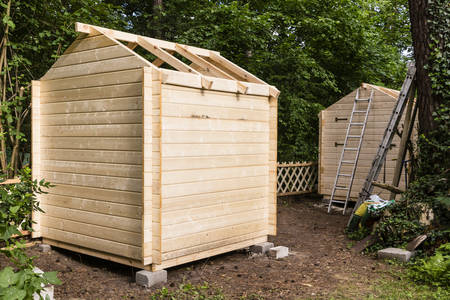 Construction of a wooden hut in a garden Stock Photo