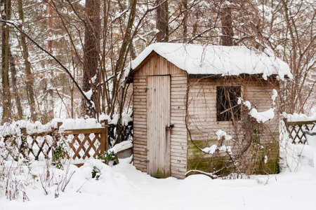 Hut with snow in a garden in winter Stock Photo