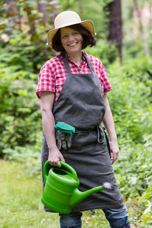 Pflanzen: gardener with watering can, sun hat and apron Stock Photo