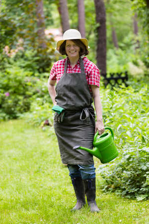sun hat: gardener with watering can, sun hat and apron Stock Photo