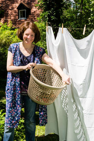 Woman Hanging up the washing in a garden photo