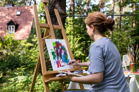 Woman painting at a canvas with paint brush and palette knife Stock Photo