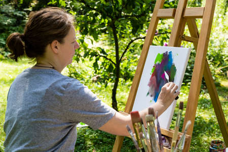 palette knife: woman is painting with palette knife in a garden