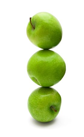 Stack of balancing green apples isolated on white photo