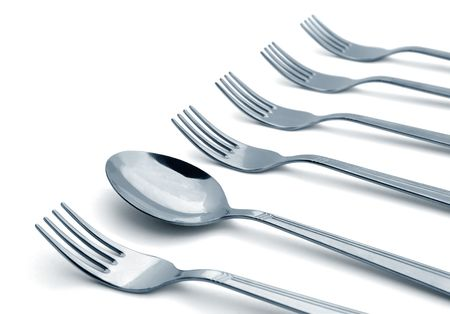 Spoon in a row of forks isolated on white Stock Photo - 6425633