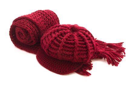 Red knitted winter wool scarf and cap isolated on white photo