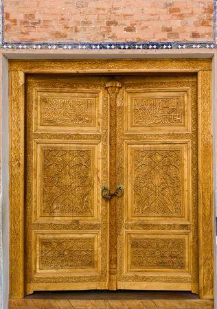 Old carved wooden door in madressah of Bukhara,  Uzbekistan photo