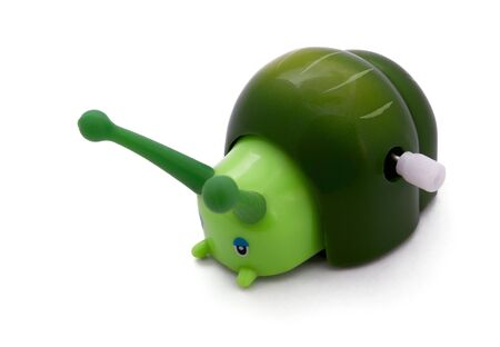 windup: Green wind-up  toy snail isolated on white Stock Photo