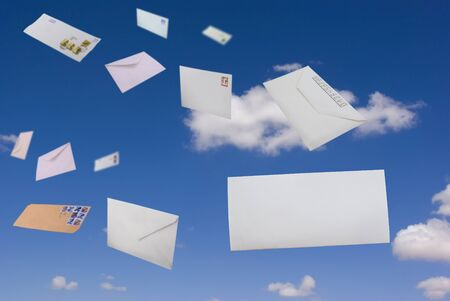Envelopes flying against the blue sky and clouds photo