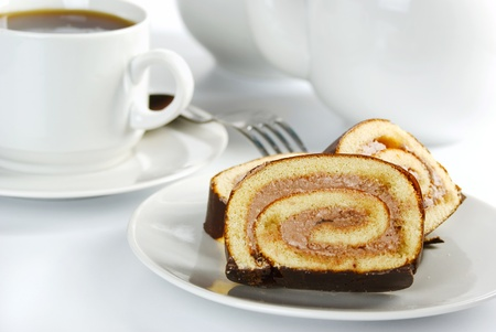 breakfast table: Slices of chocolate roll on a plate and cup of tea
