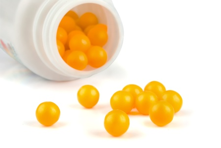 Round yellow pills in plastic container isolated on white  Stock Photo - 8679511