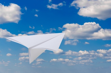 Paper airplane flying against blue sky and clouds photo